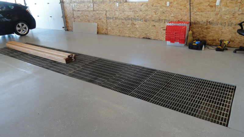 Grate covered pit in garge floor in one of the bays of garage