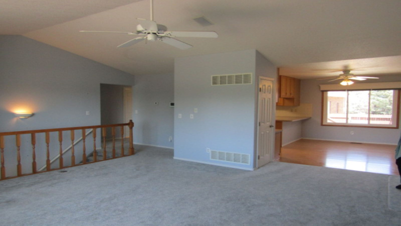 View of dining room, hallway to bedrooms and basement stairs from living room